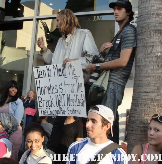 a homeless former spiderman holding up a sign that says jennifer aniston made me homeless at the horrible bosses world movie premire in hollywood