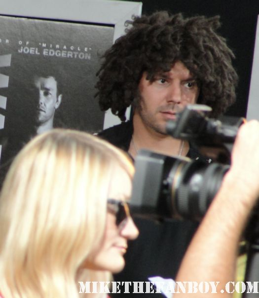 a man with really crazy afro like hair on the red carpet at the warrior premiere in hollywood the warrior premiere in hollywood the warrior world movie premiere with Tom hardy joel edgerton rare hot sexy promo red carpet photo bane dark knight rises