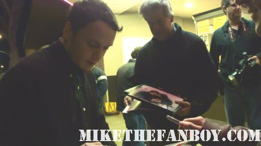 anton yelchin signing autographs for fans before  at a q and a with felicity jones at the aero theater in santa monica ca