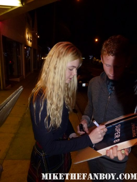 elle fanning from super 8 and we bought a zoo signing autographs for fans outside a screening in santa monica looking awesome