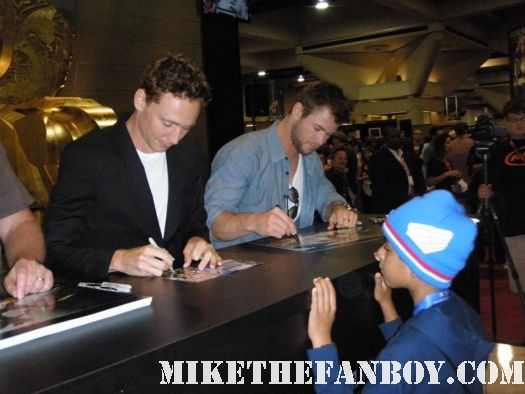 tom hiddleston and Chris hemsworth signing autographs at the marvel booth at san diego comic con