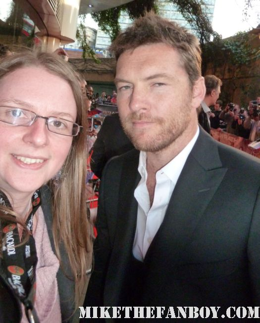 sam worthington poses for a fan photo with mike the fanboy's scarlet starlet at the wrath of the titans world movie premiere