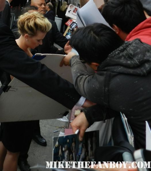 sexy scarlett johansson black widow  signs autographs for fans at the avengers world movie premiere on the red carpet with chris hemsworth chris evans samuel l jackson and more