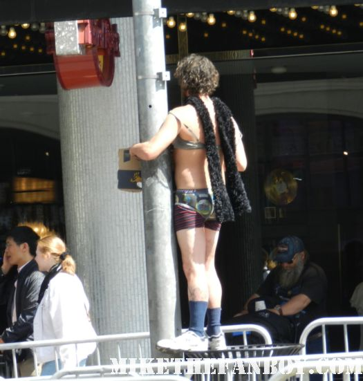 a naked homeless man doing a striptease on hollywood blvd. the crowd of people waiting at the dark shadows world movie premiere for johnny depp and michelle pfeiffer