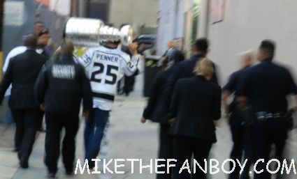 penner from the los angeles kings walking out of the jimmy kimmel show and showing fans the stanley cup after a talk show taping