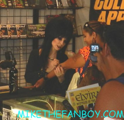 elvira autographing a fans arm tattoo elvira mistress of the dark signing autographs for fans at golden apple comics in los angeles looking hot and sexy elvira arriving in front of golden apple comics to sign autographs for fans looking hot and sexy elvira mistress of the dark