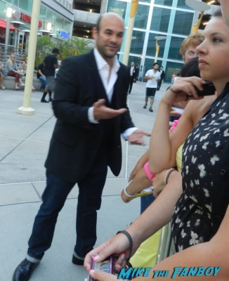 ian gomez from cougar town signing autographs for fans at the words movie premiere with bradley cooper and zoe saldana