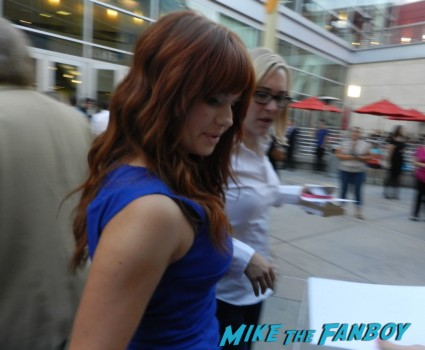 red headed disney chick signing autographs for fans at the words movie premiere with bradley cooper and zoe saldana