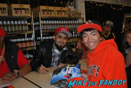 Sergio Romo and E40 signing autographs and taking fan photos tor toys for tots in the san francisco bay area rare promo signed autographs