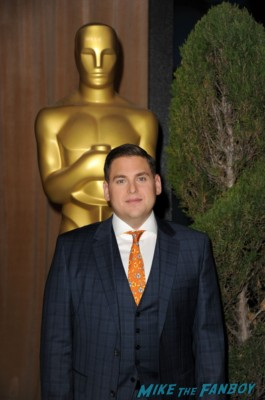 academy award nominee jonah hill posing in front of a oscar statue at the awards show