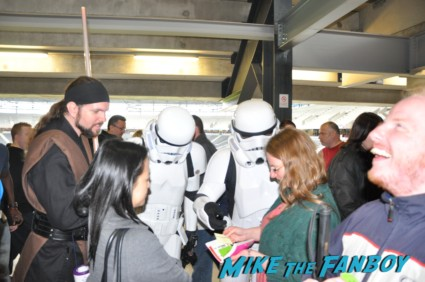 Stormtroopers looking at autograph tickets at collectormania in london while waiting for Brian Blessed
