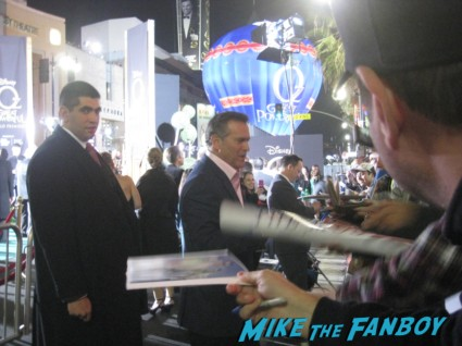 bruce campbell signing autographs for fans Oz the great and powerful movie premiere red carpet with james franco mila kunis michelle williams