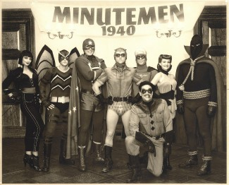 """Watchmen Minutemen 1940 from the mystery adventure """"Watchmen,"""" a Warner Bros. Pictures and Paramount Pictures presentation, in association with Legendary Pictures.  Pictured left-to-right are: APOLLONIA VANOVA as Silhouette, NIALL MATER as Mothman, DAN PAYNE as Dollar Bill, CLINT CARLETON as the original Nite Owl, DARYL SCHEELER as Captain Metropolis, CARLA GUGINO as the original Silk Spectre, GLENN ENNIS as Hooded Justice and (kneeling) JEFFREY DEAN MORGAN as The Comedian. PHOTOGRAPHS TO BE USED SOLELY FOR ADVERTISING, PROMOTION, PUBLICITY OR REVIEWS OF THIS SPECIFIC MOTION PICTURE AND TO REMAIN THE PROPERTY OF THE STUDIO. NOT FOR SALE OR REDISTRIBUTION."""