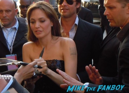 Angelina Jolie signing autographs for fans at the premiere of Salt
