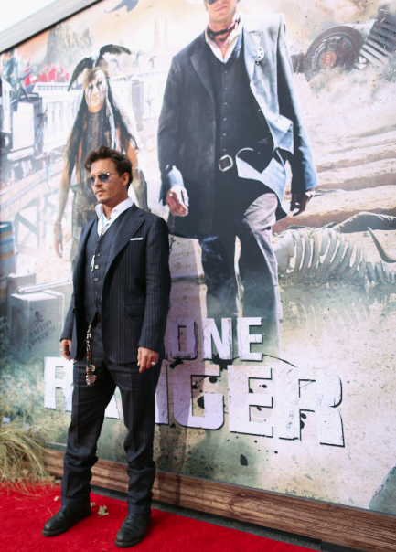 Johnny Depp on the red carpet at the Lone Ranger Movie Premiere signing autographs