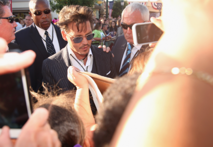 johnny depp signing autographs on the red carpet at the Lone Ranger Movie Premiere signing autographs
