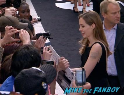 Angelina Jolie signing autographs for fans World War z movie premiere london brad pitt angelina jolie signing autographs red carpet (11)