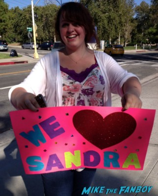 Fans holding up signs to try and meet sandra bullock