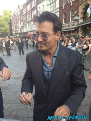 Johnny Depp signing autographs for fans at the uk premiere of The Lone Ranger