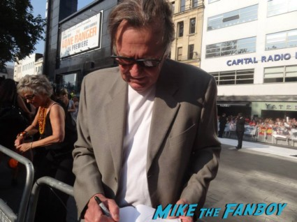 Tom Wilkinson signing autographs for fans at the uk premiere of The Lone Ranger