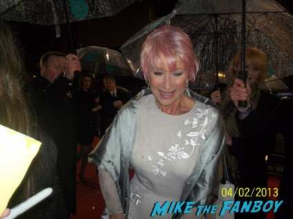 Dame Helen Mirren with pink hair signing autographs