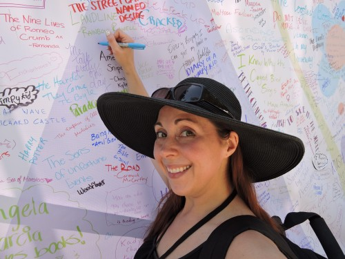 """Novel Strumpet signing the """"What are you Reading"""" wall"""