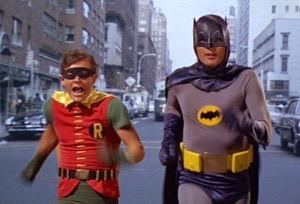 batman and robin running through the street