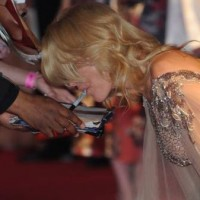 gillian anderson signing an autograph with her mouth